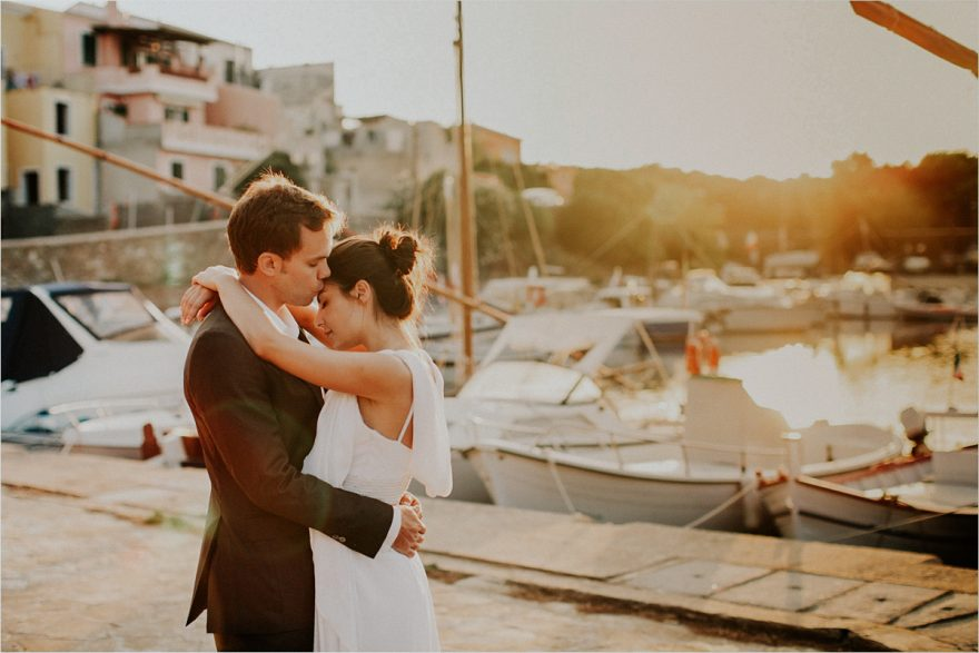 bride and groom posing for a photo during the golden hour after their destination wedding in Sardinia Italy