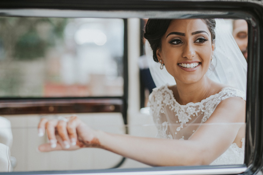 asain bride looking through her car window during her hindu wedding in Hatfield House in Hertfortshire