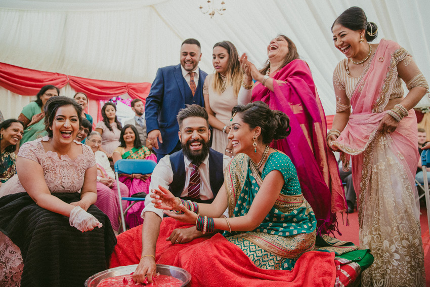 bride and groom playing games during their indian asian wedding