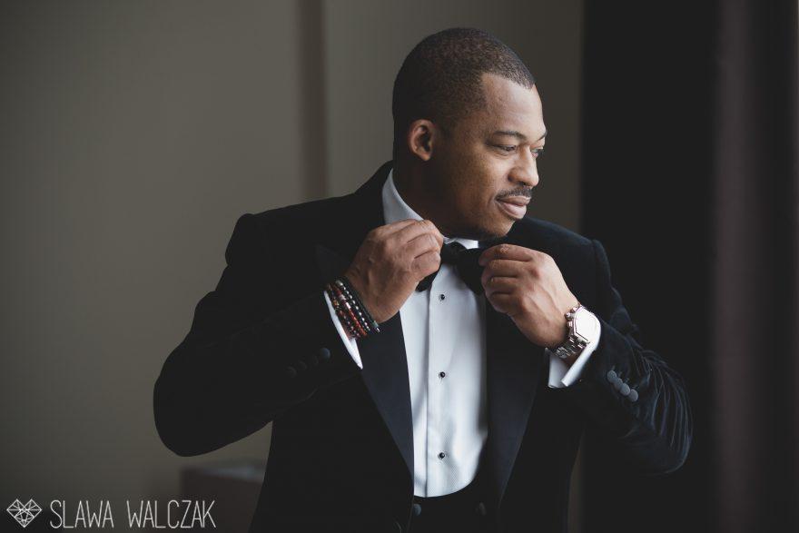 groom correcting his bow tie