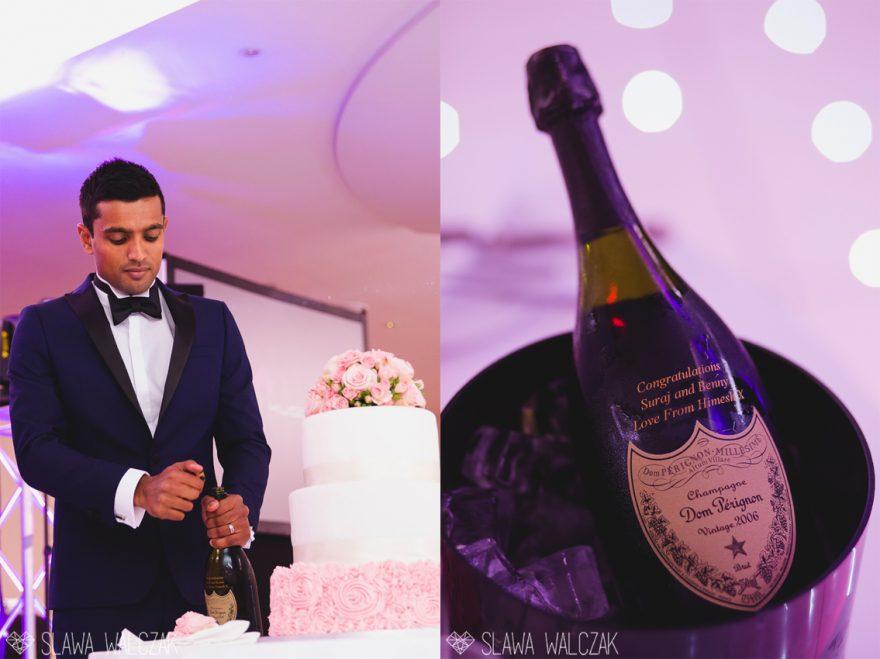 elegant groom opening a celebratory bottle of champagne