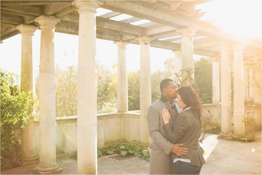 future grook kissing his fiance in Hampstead Heath Pergola