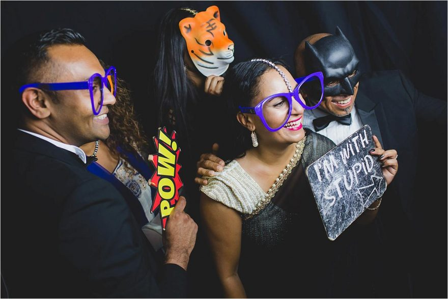 wedding guests posing for photos in a photobooth