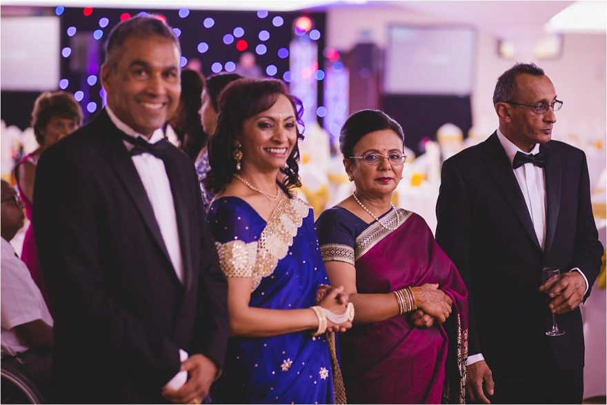 bride and grooms parents welcomong guests at an indian wedding