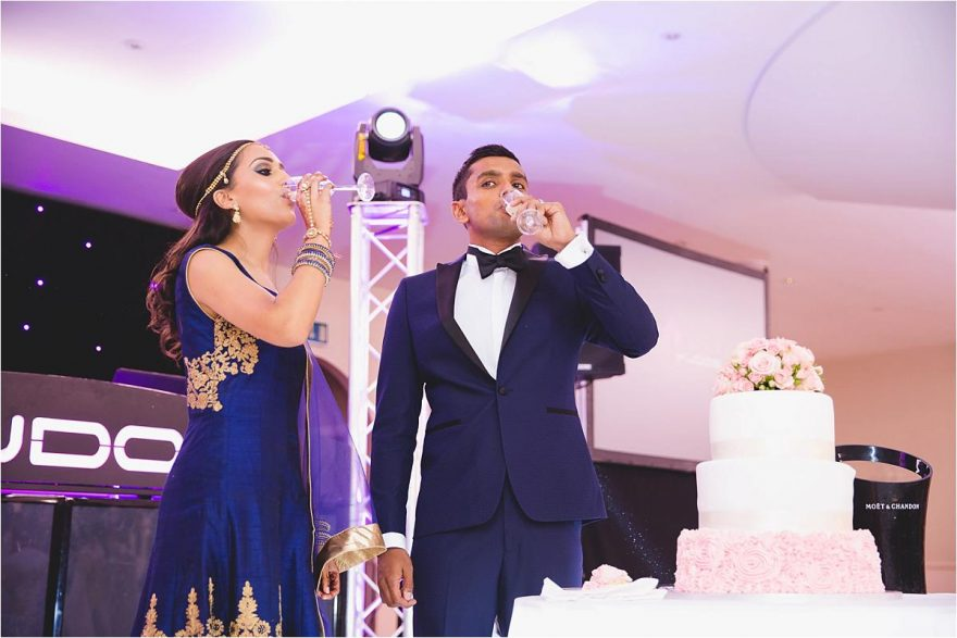 elegant asian couple drinks champagne at their hindu wedding
