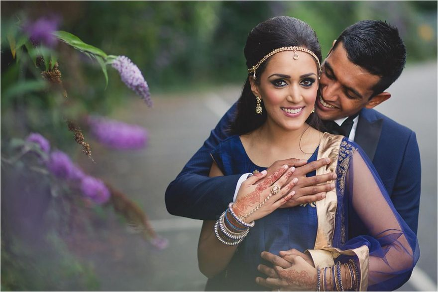 indian couple cute wedding photo groom embracing bride