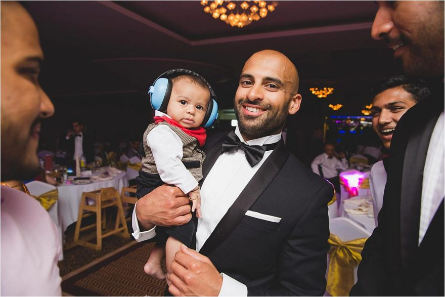 cute baby with earphones at an asian wedding party