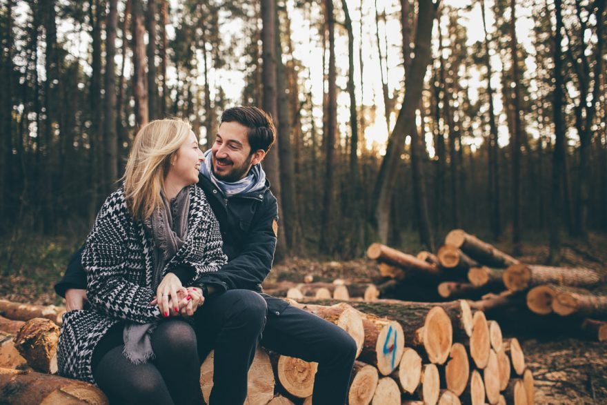 a couple sosing for their destination engagement photos in the woods