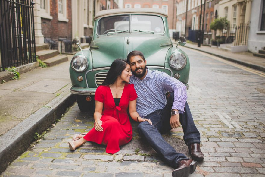 south asian indian couple posing for their engagement photos in front of a vintage car