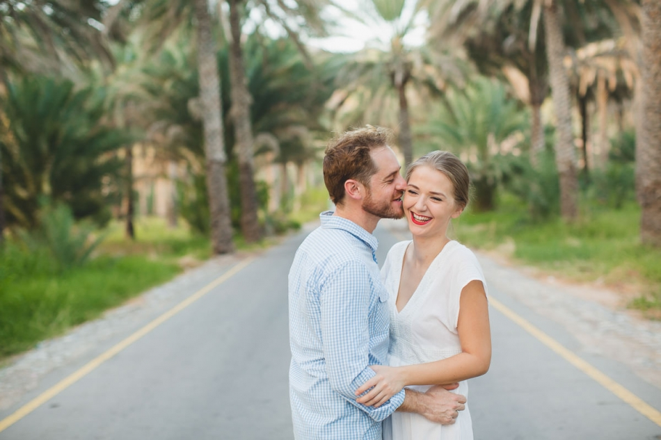 couple kissing and giggling between palm trees in muscat oman for their engegement photos