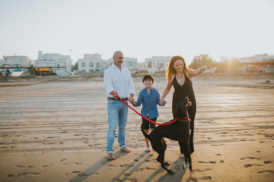 expat family playing with their dog during a beach familly photo session in Muscat Oman