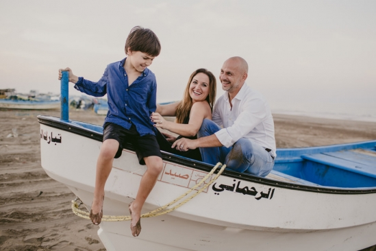 family posing for a photo in a boat on seeb beach in Muscat Oman