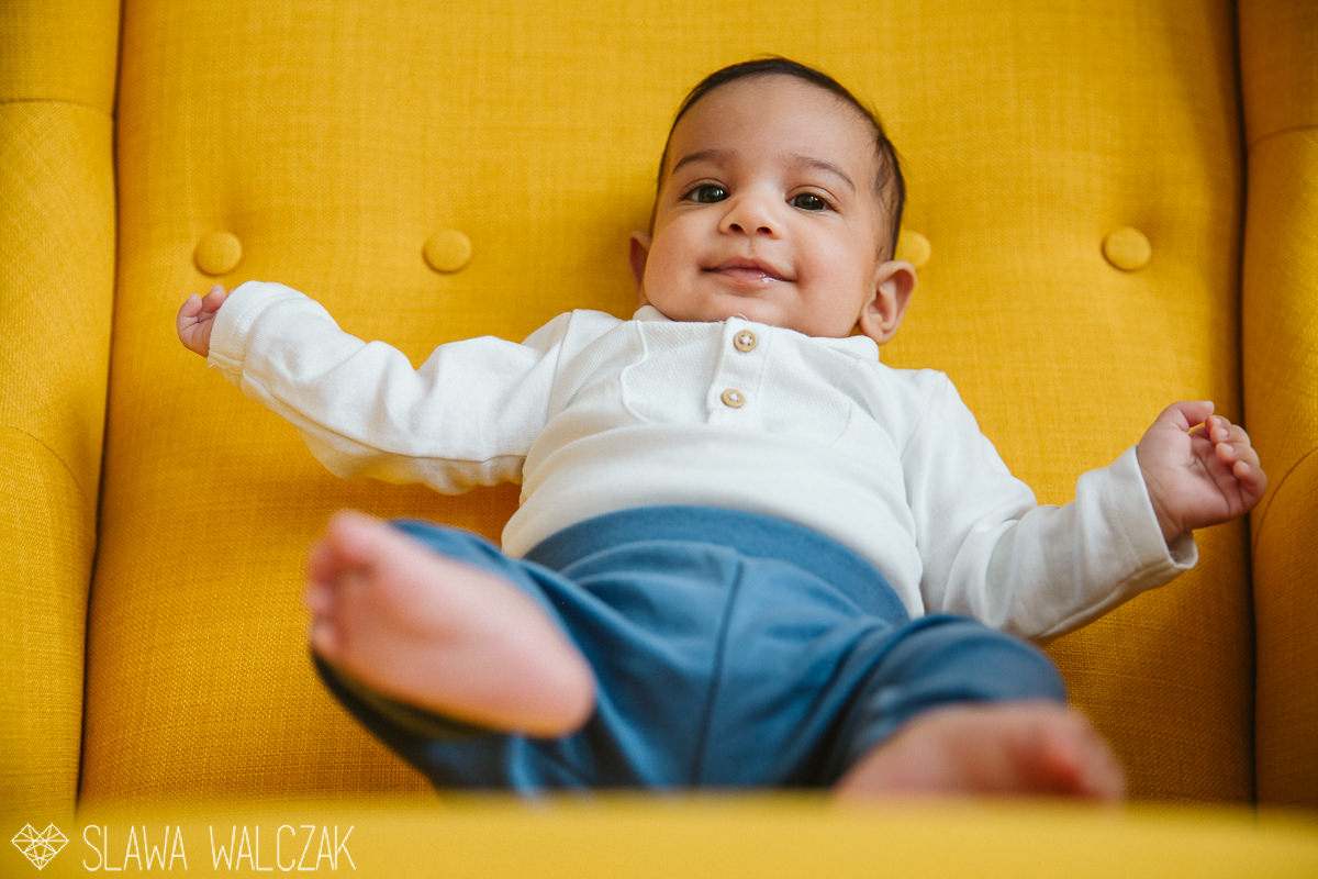 baby smiling while posing for his newborn photograhy in London