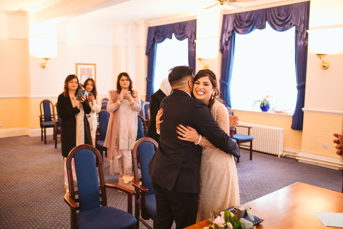 very happy asian bride hugs her husband during a wedding at Ealing Town Hall