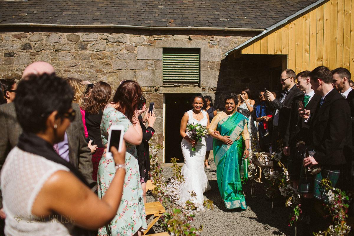 bride and her mum walk down the aisle at an Edinburgh Farm Wedding