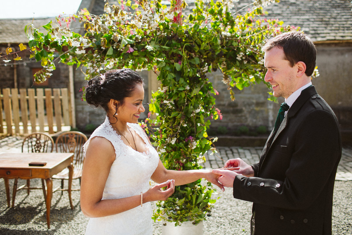 bride and groom exchange rings during an outdoor wedding in Cockdurno Farm