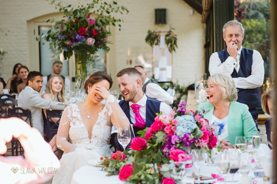 bride and groom smiling at the speeches in the Dairy Wedding in Waddesdon