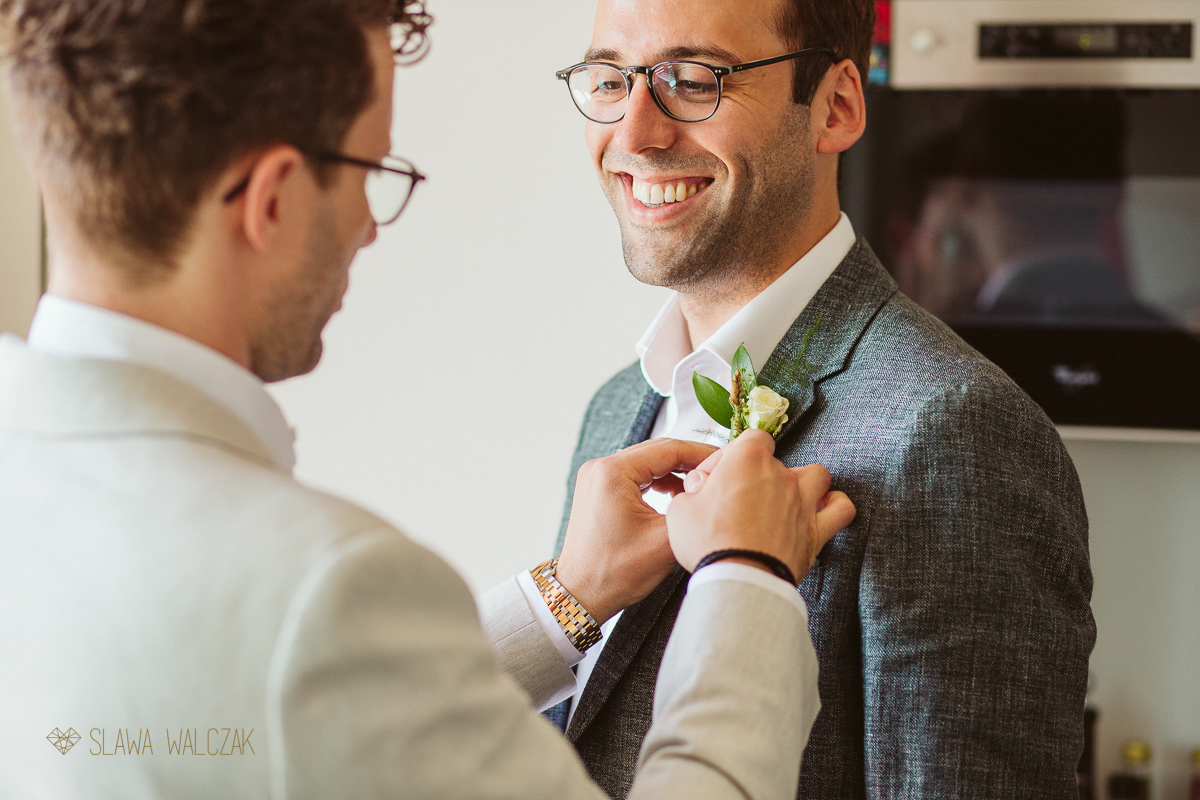 gay guys putting up ther button holes flowers