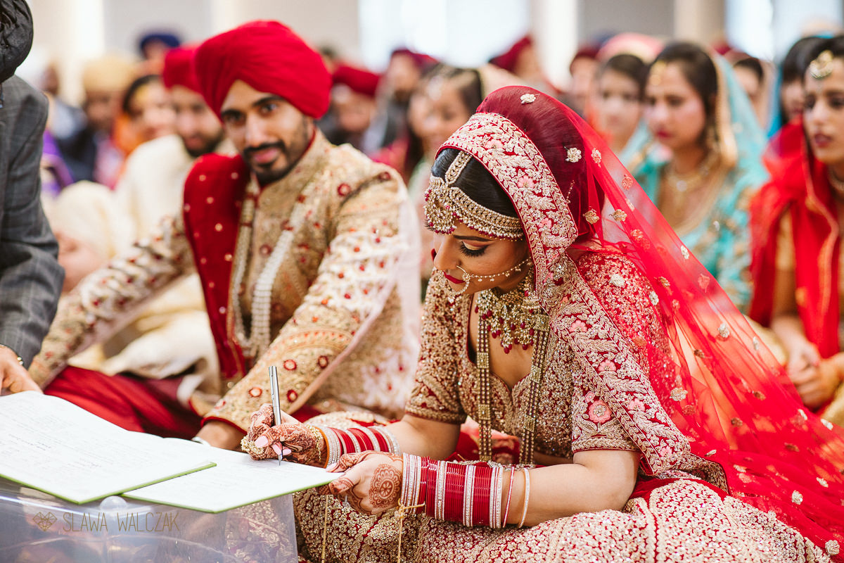 bride signing a registry during his sikh marriage ceremony