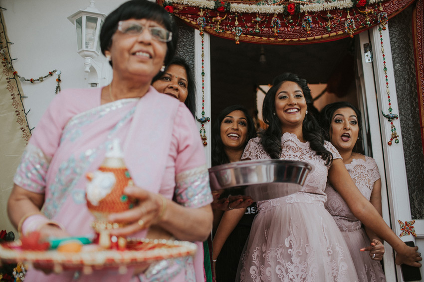 bridesmaids and family awaiting an asian hindu couple for their arrival home after the wedding ceremony