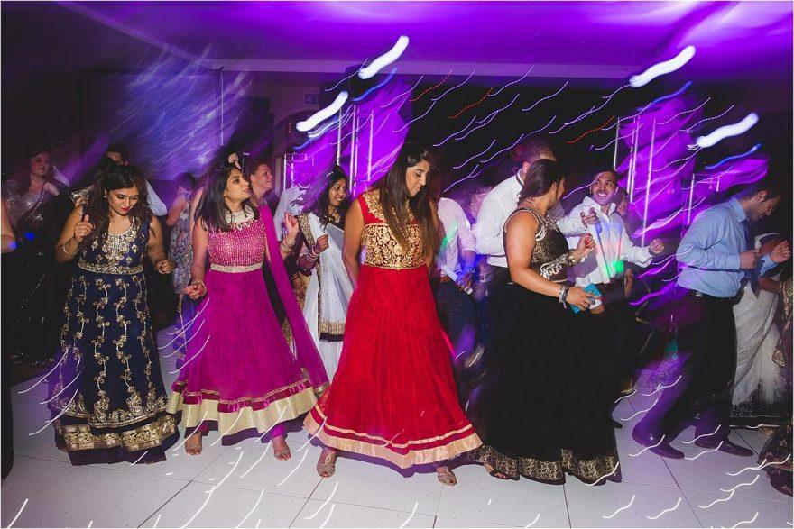 asian ladies dancing at a wedding reception