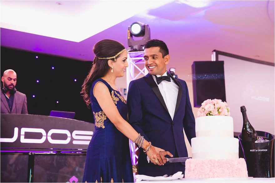 couple smiling to each other while cutting their wedding cake