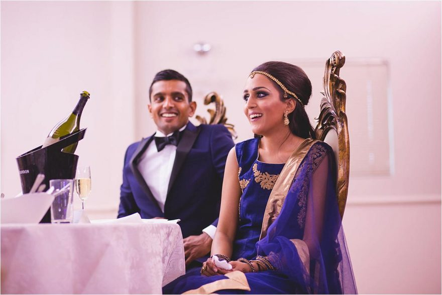 bride and groom laughing during asian wedding speaches