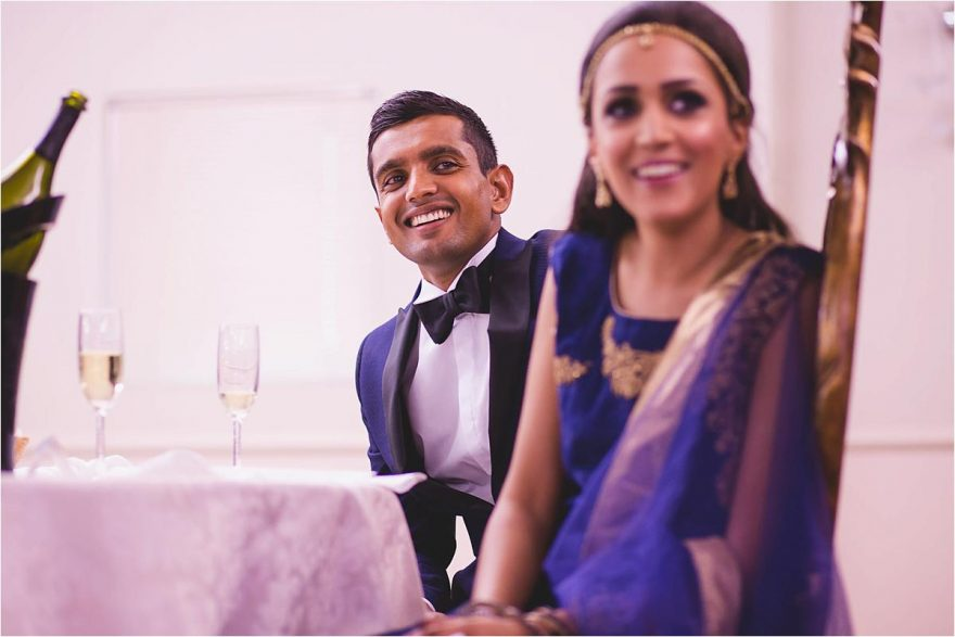 bride and groom laughing at funny wedding speaches