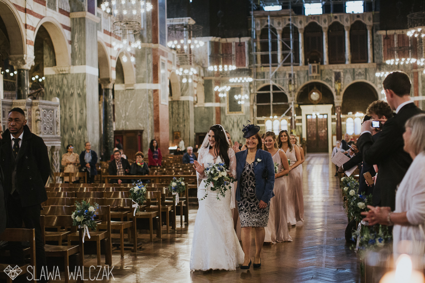 bride is entering a westminster cathedral with her mum and bridesmaids