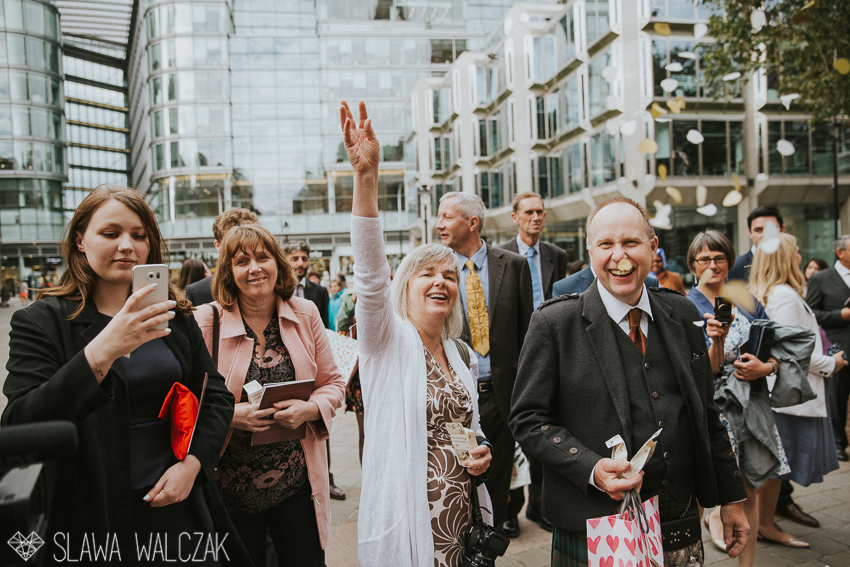 guests throwing confetti outside the westminster cathedral