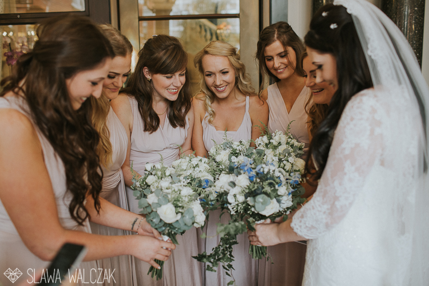 bride and her bridesmaids admiring their bridal flowers