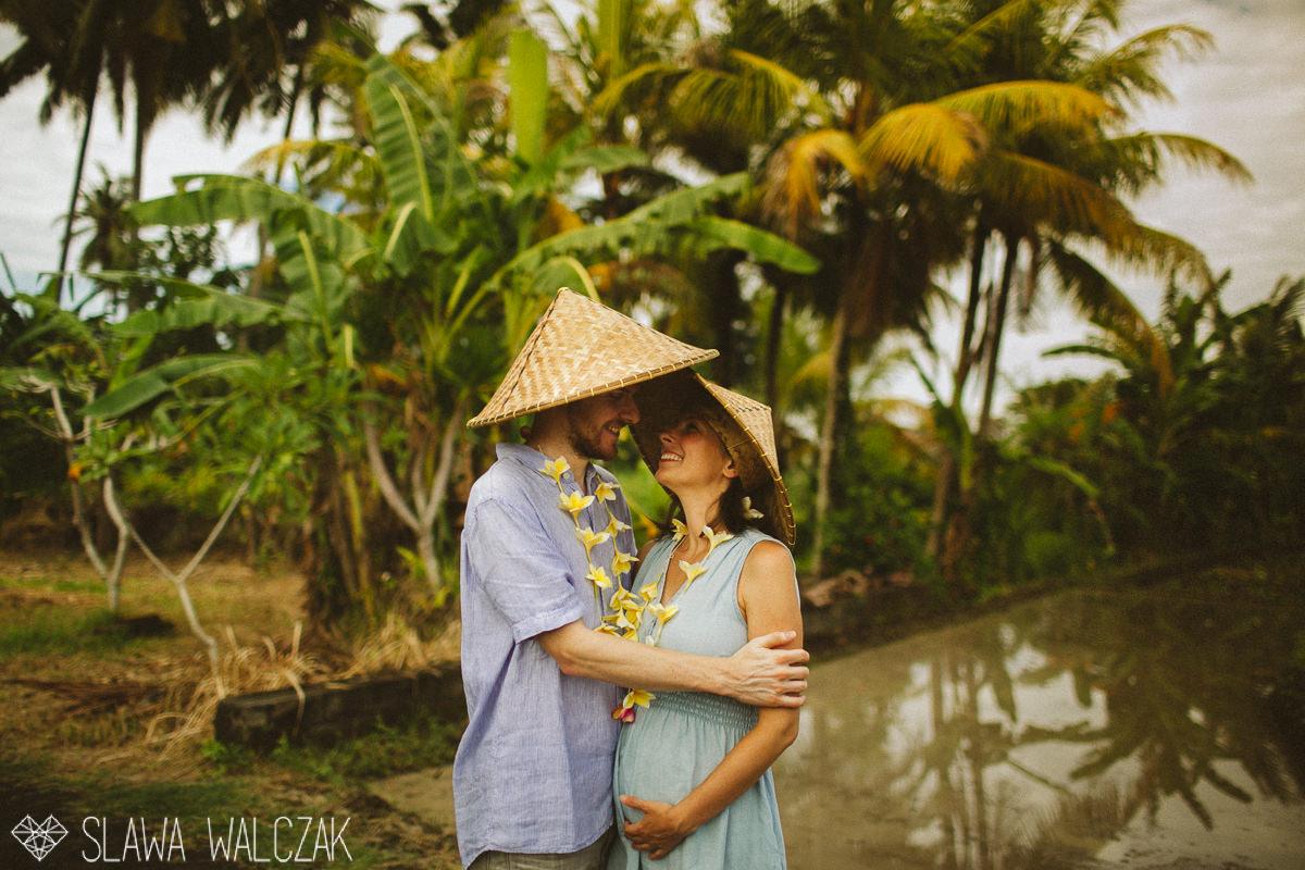 couple posing for ttheir engagemen, maternity photos in between palm trees in Ubud, Bali