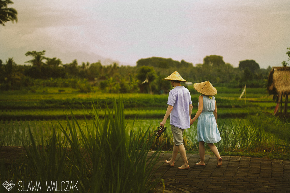 couple walking through rice paddy fileld in Ubud Bali for their engagement photo session
