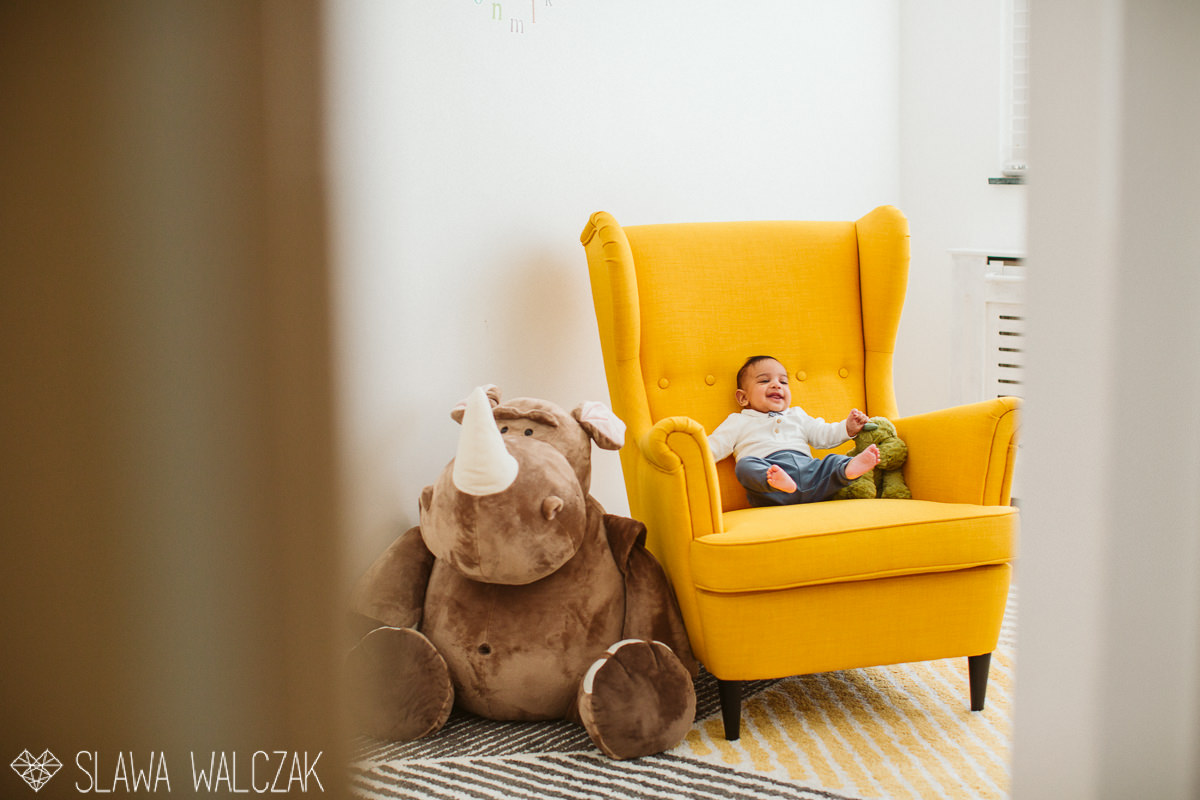newborn baby giggles in a stylish yellow armchair during a lonfon family photography session