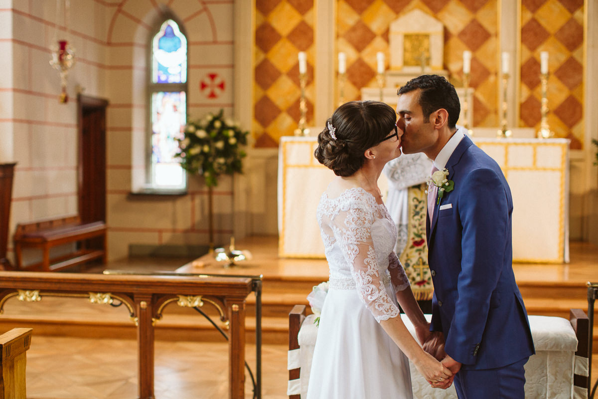 couple first kiss at Kensal Rise church during a London wedding