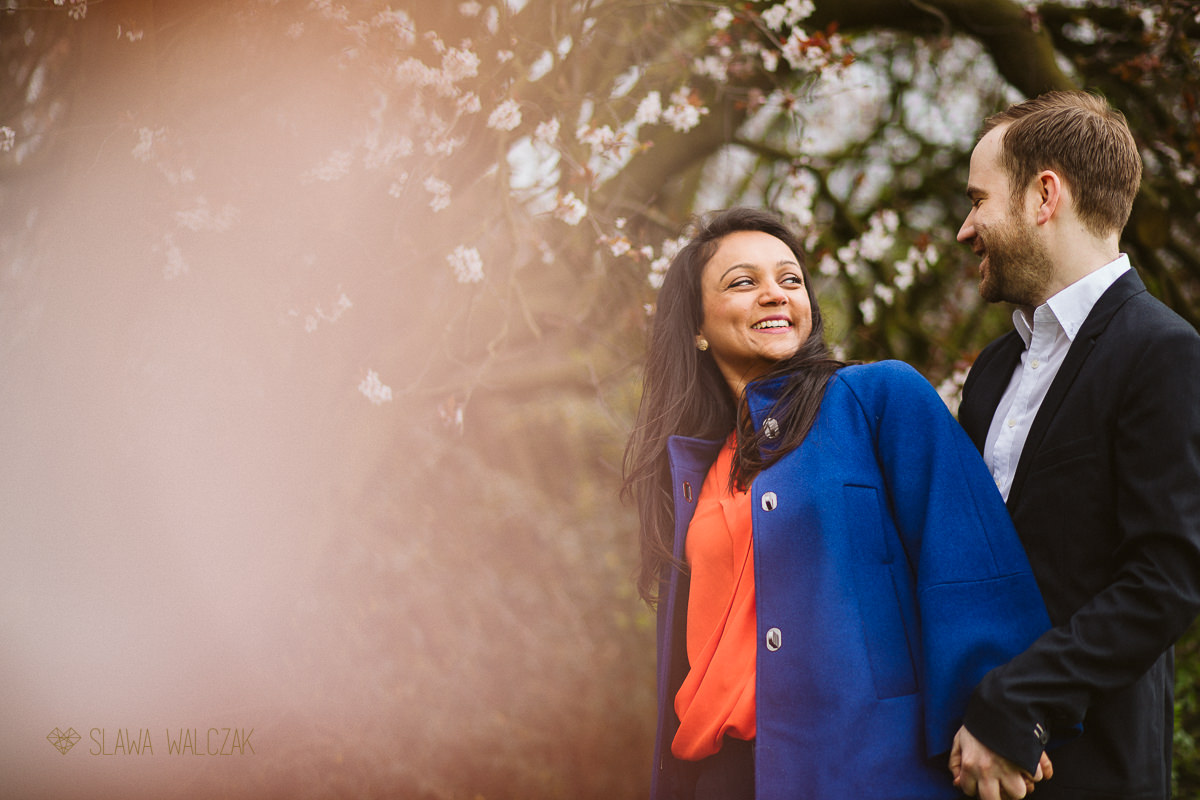 relaxed and fun couple posing for their engagement photos in the bloom of Dulwich park