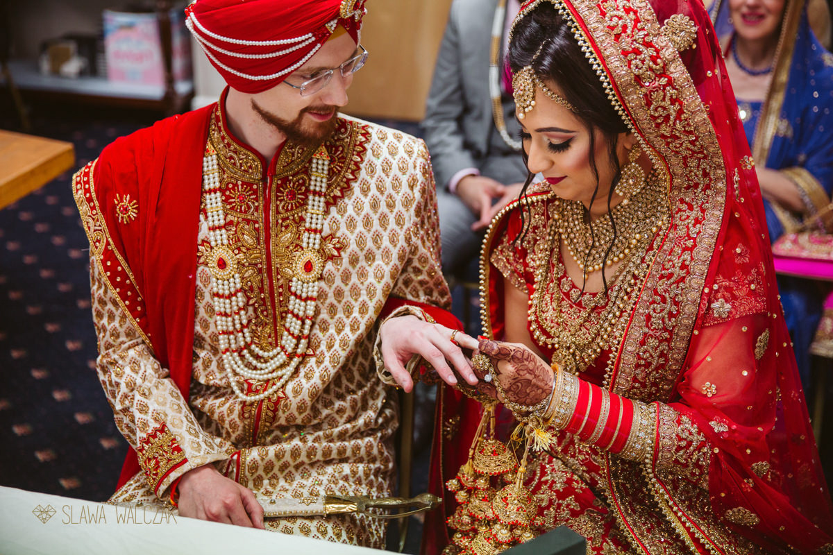 indian couple exchanges rings during their sikh wedding ceremony