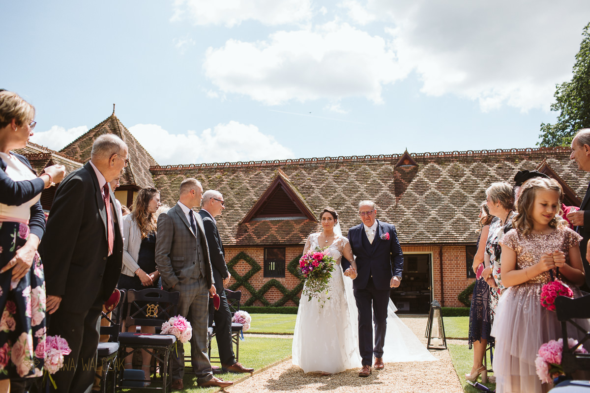 father walking the bride at an outdoor wadding in the Dairy in Waddesdon