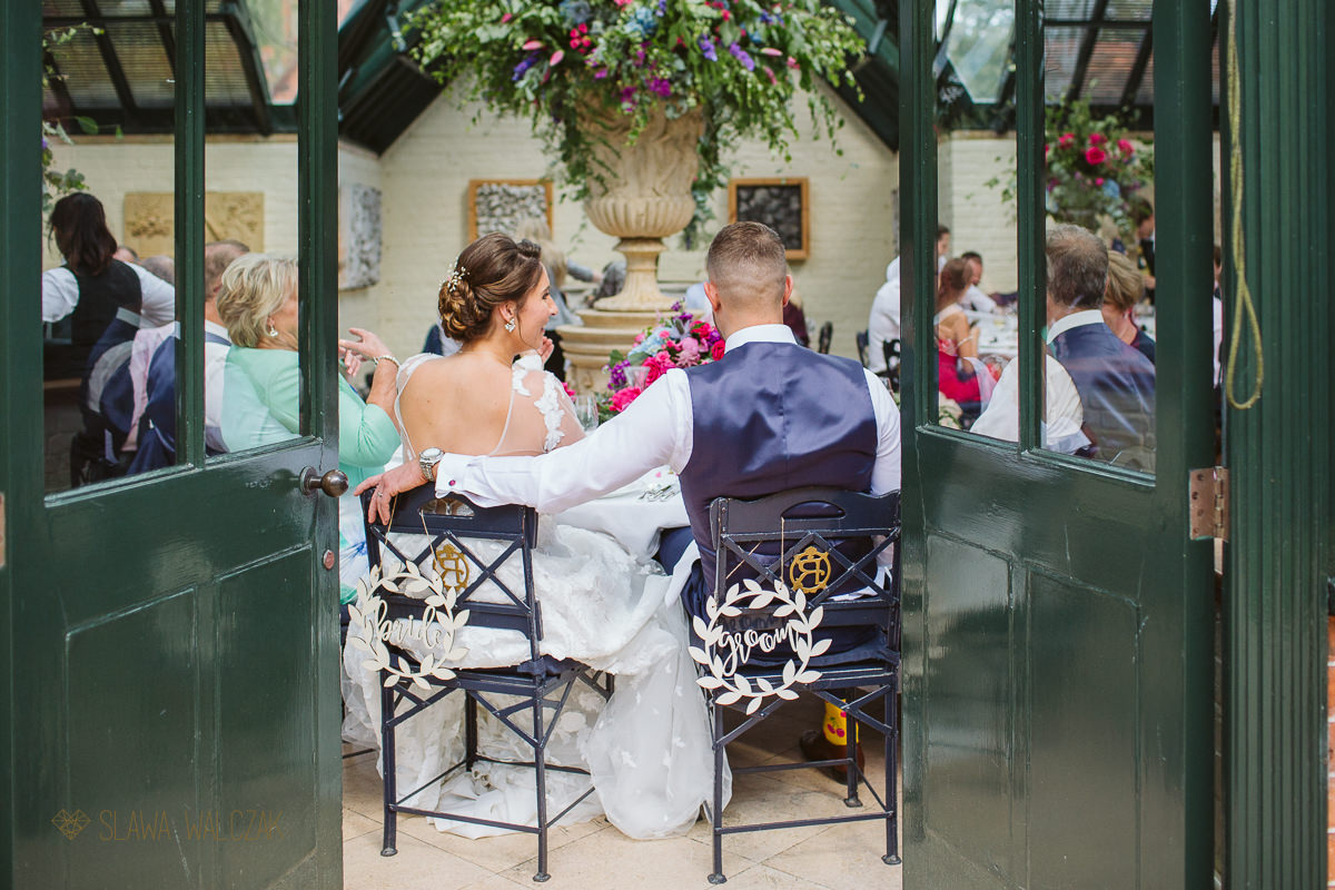 bride and groom aittig at their reception table at the Dairy in Waddesdon