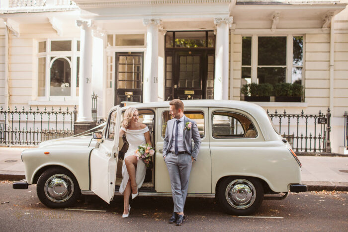 London couple posing in front of the cab outside Old Marylebone Town Hall