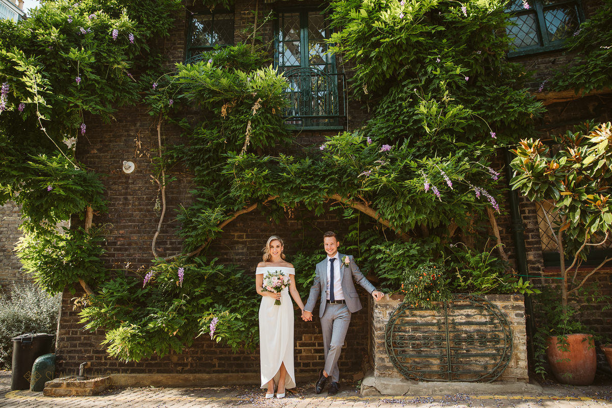 bride and groom posing for their pre wedding photos in Kynence Mews in London
