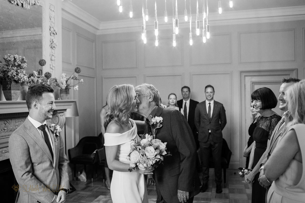 father kissing the bride during a wedding ceremony