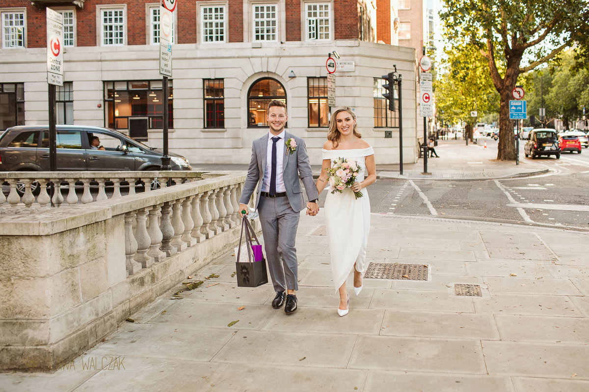 gourgeous bride and groom walking with smiles towards the Old Marylebone Town Hall